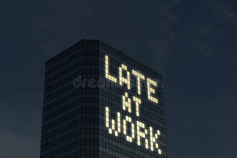 Late at work concept. Working overtime and extra hours. Tired and stressed from too much things to do at job. Text made by office building window lights at stock image