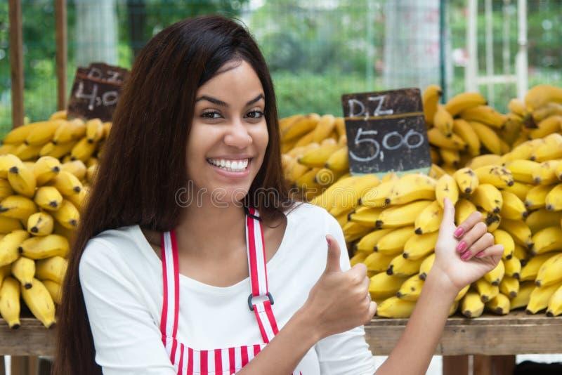 Lateinamerikanische Verkäuferin am Landwirtmarkt mit Bananen lizenzfreie stockfotografie