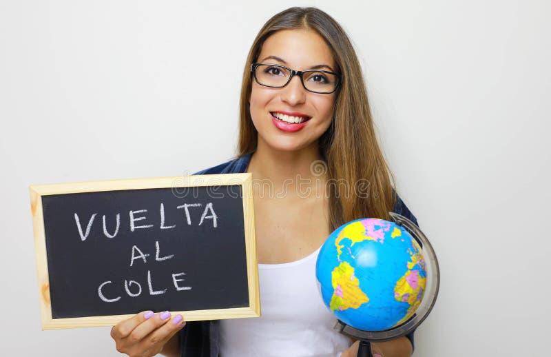 Lateinische junge Holdingkugel und -tafel des weiblichen Lehrers mit Spanisch geschrieben lizenzfreie stockfotografie