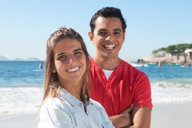 Lateinische Paare am Strand, der Kamera betrachtet lizenzfreies stockfoto