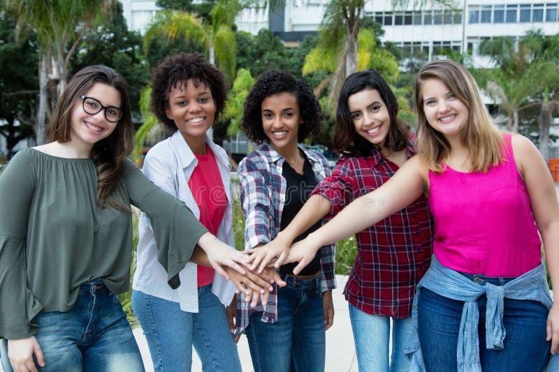 5 lateinische und Kaukasier- und Afroamerikanerfrauen halten zusammen stockbild