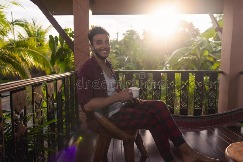Lateinischer Mann, der auf Sommer-Terrassen-Griff-Schalen-glücklichem draußen lächeln, Guy In Morning Drinking Coffee sitzt lizenzfreie stockfotos