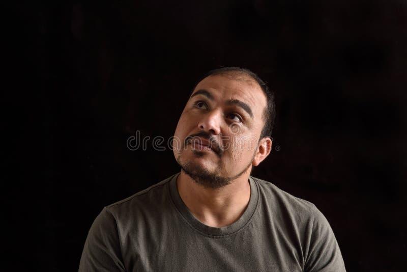 Lateinischer Mann, der oben auf Schwarzem schaut lizenzfreie stockfotos