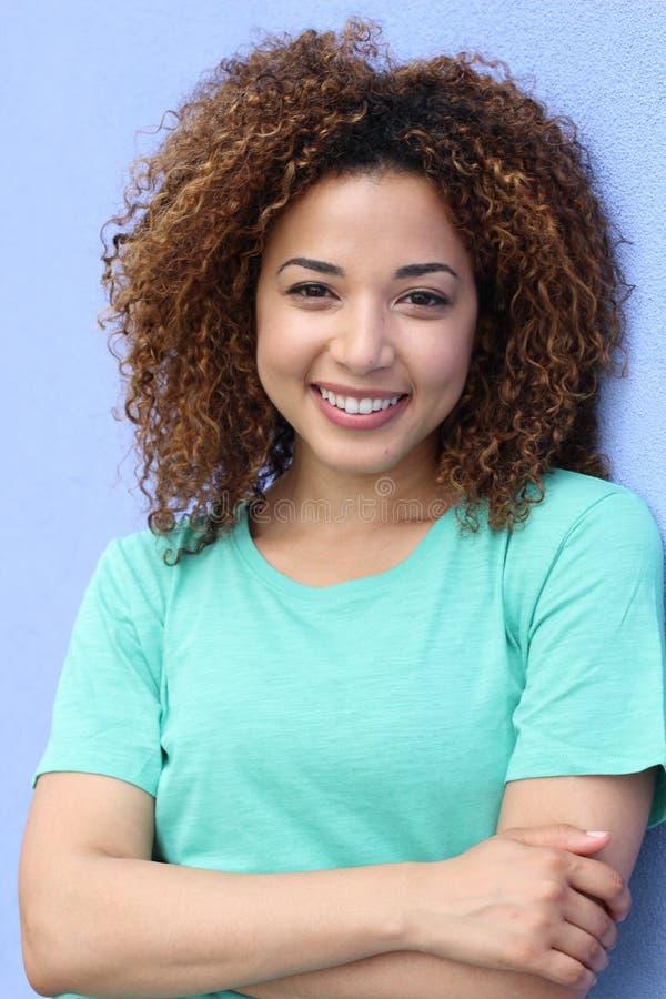 Lateinisches Mädchen mit lächelndem Porträt der blonden Afrofrisur auf einem blauen Hintergrund stockfotos