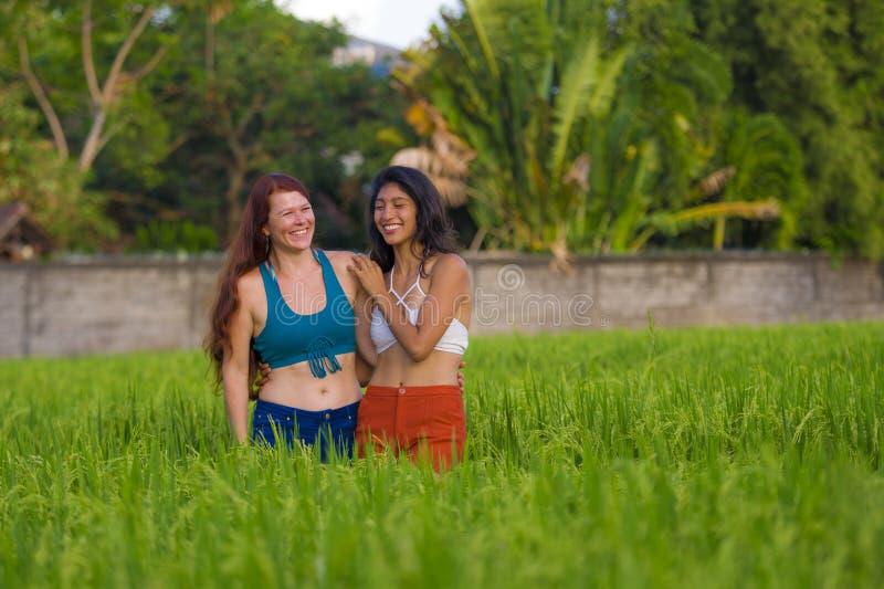 Lateinisches M?dchen und ihre attraktive kaukasische Freundin beide Frauen, welche zusammen die Sommerferien haben Spa? auf dem R lizenzfreie stockfotografie