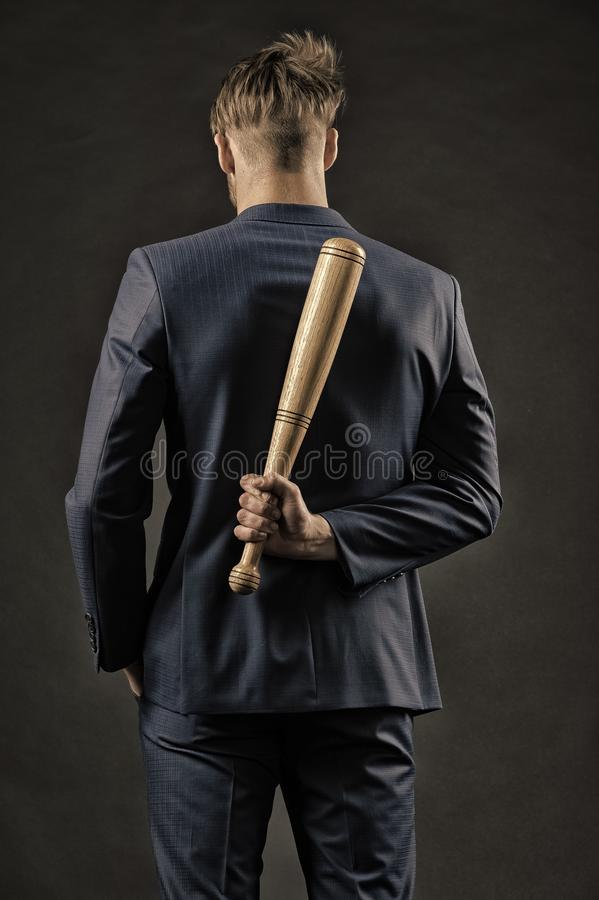 Latent aggression. Man with bat hides his aggression slow down and keep calm, rear view. Businessman or man in formal royalty free stock image