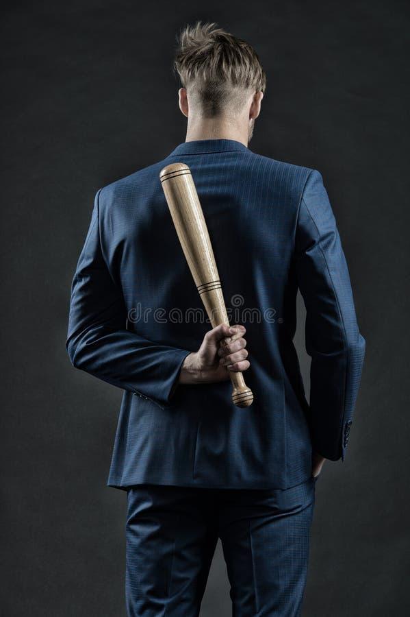Latenter Angriff Mann mit Schläger versteckt seine Angriffsverlangsamung und hält ruhige, hintere Ansicht Geschäftsmann oder Mann lizenzfreies stockfoto