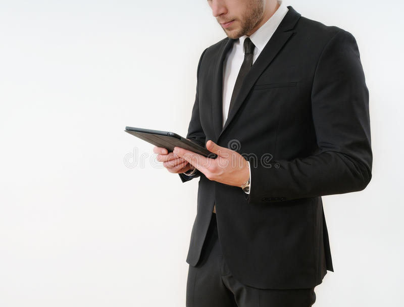 Lateral de carrocería del hombre de negocios en el traje negro que sostiene su tableta en blanco fotos de archivo libres de regalías