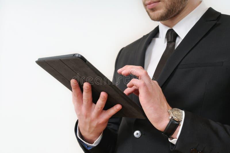 Lateral de carrocería del hombre de negocios en el traje negro que sostiene su tableta en blanco fotos de archivo