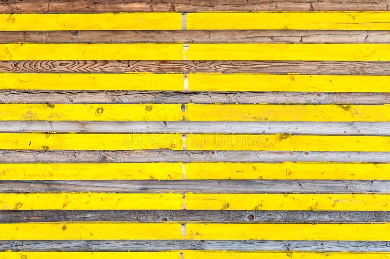 Lateral wooden planks with alternating yellow color and natural texture stock photos