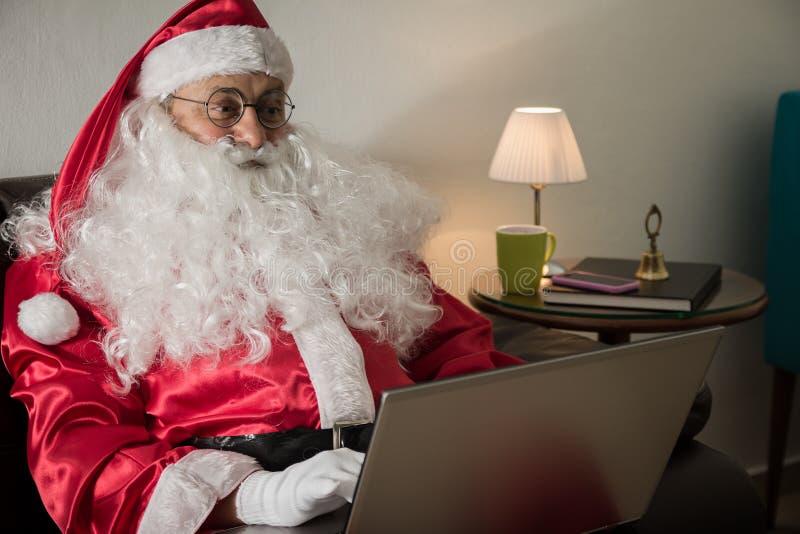 Lateralmente di Santa Claus che si rilassa in sofà a casa facendo uso del computer portatile FO immagini stock