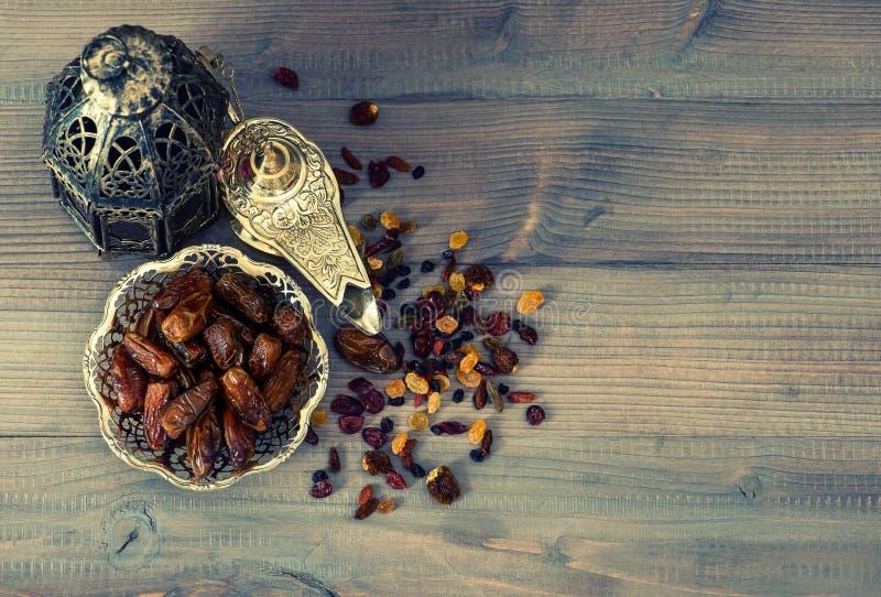 Latern orientale d'annata, uva passa e datteri su fondo di legno immagine stock