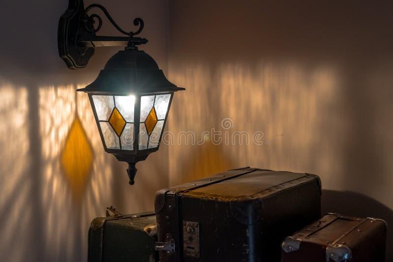 Latern viejo en una pared y las maletas imagen de archivo