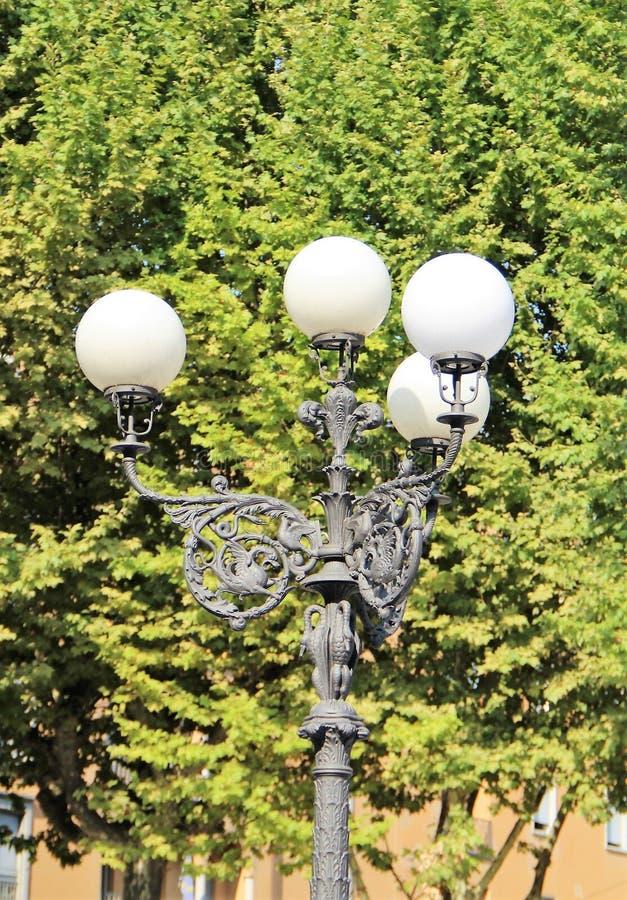 Laterne auf dem Hintergrund des grünen Laubs der Bäume in der Stadt von Lucca, Italien lizenzfreies stockbild