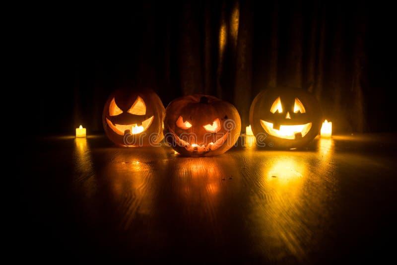 Laterne der Halloween-Kürbiskopf-Steckfassung O mit glühenden Kerzen auf Hintergrund Kürbise auf Bretterboden stockbilder