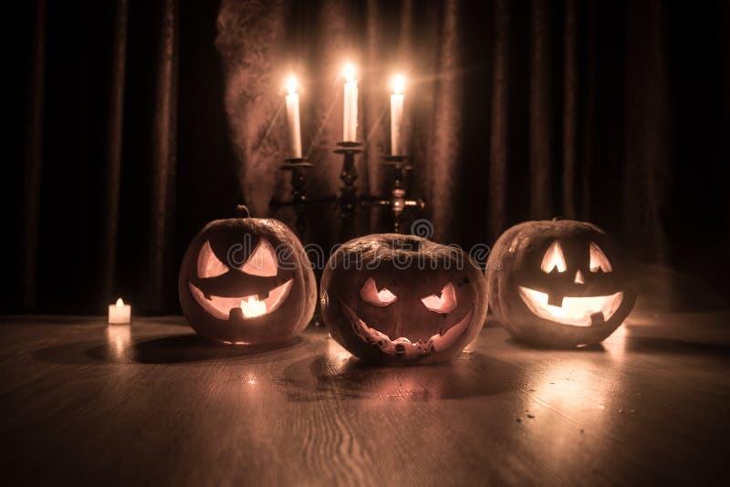 Laterne der Halloween-Kürbiskopf-Steckfassung O mit glühenden Kerzen auf Hintergrund Kürbise auf Bretterboden stockbild