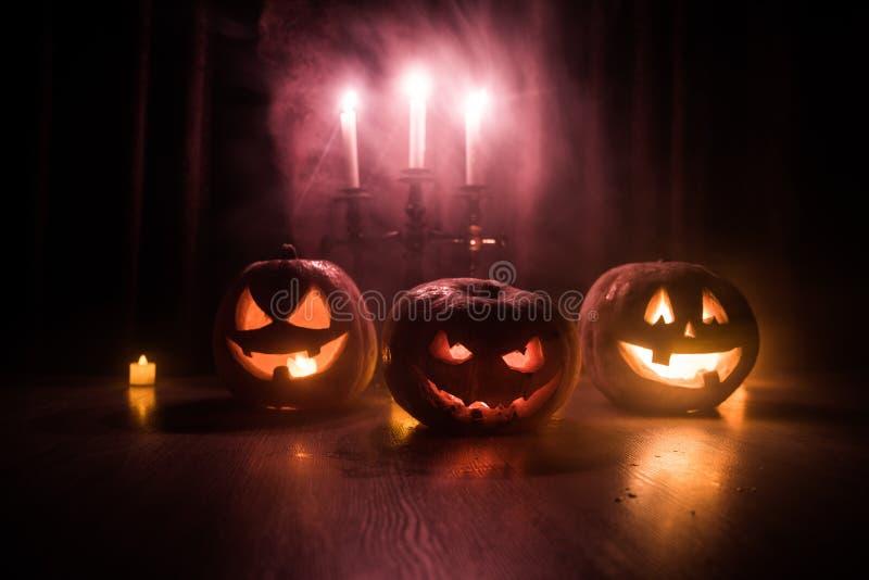 Laterne der Halloween-K?rbiskopf-Steckfassung O mit gl?henden Kerzen auf Hintergrund K?rbise auf Bretterboden lizenzfreies stockbild