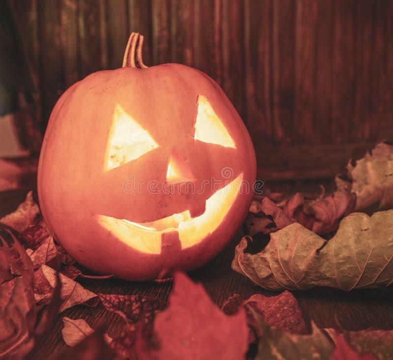 Laternen Jacks O Halloween-K?rbisgesicht auf h?lzernem Hintergrund lizenzfreie stockbilder