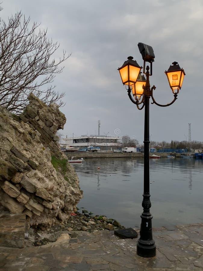 Laternenpfahl nahe einem Felsen und einem Meer mit Gebäude und Boote im Hintergrund stockfotografie