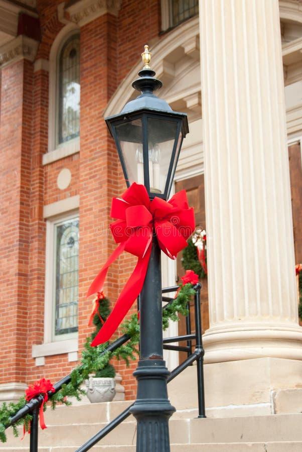 Laternenpfahl verziert mit rotem Band für Weihnachten lizenzfreie stockbilder