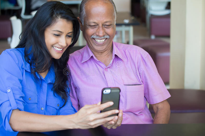 Latest action and news. Closeup portrait elderly gentleman in pink shirt and lady in blue top family enjoying mobile phone fun, isolated indoors background royalty free stock images