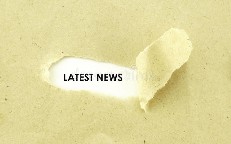 LATEST NEWS. Text LATEST NEWS appearing behind torn light brown envelope royalty free stock photography