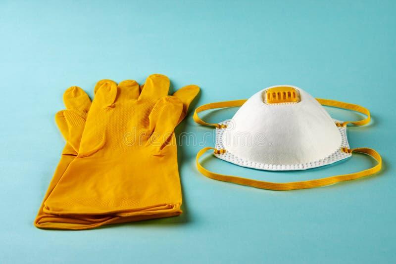 Latex-handskar och mask för kirurgiska ingrepp på blå bakgrund royaltyfri bild