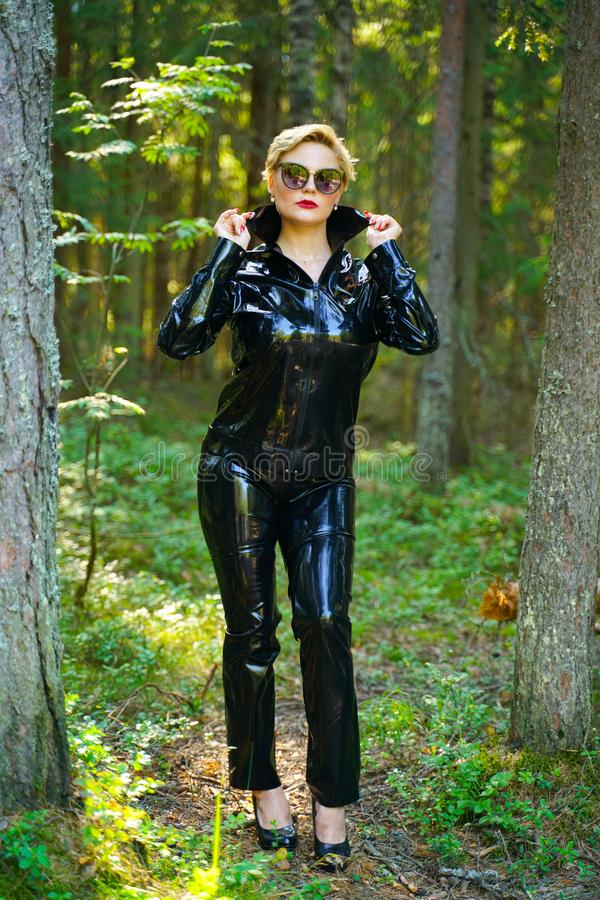 Latex rubber fashion woman walking in the forest. Bad girl wearing black shiny costume as protect and walking alone in the green hot summer forest royalty free stock photo