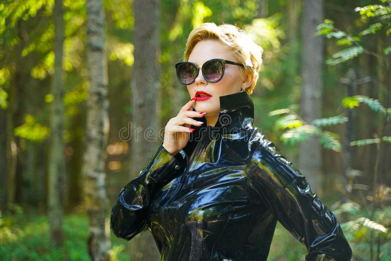 Latex rubber fashion woman walking in the forest. Bad girl wearing black shiny costume as protect and walking alone in the green hot summer forest stock photo