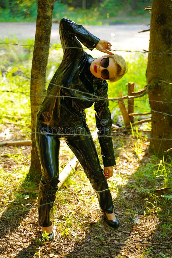 Latex rubber fashion woman walking in the forest. Bad girl wearing black shiny costume as protect and walking alone in the green hot summer forest royalty free stock photos
