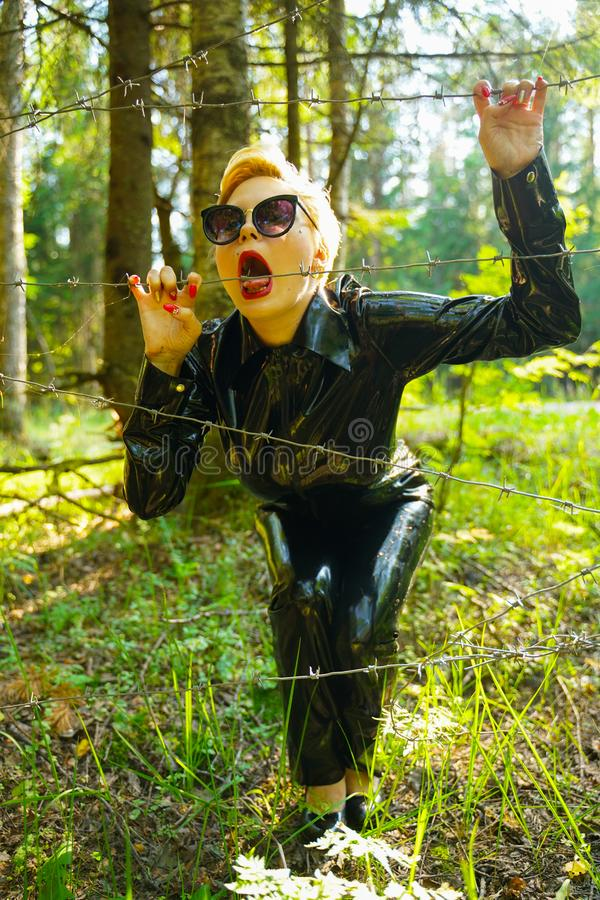 Latex rubber fashion woman walking in the forest. Bad girl wearing black shiny costume as protect and walking alone in the green hot summer forest stock images