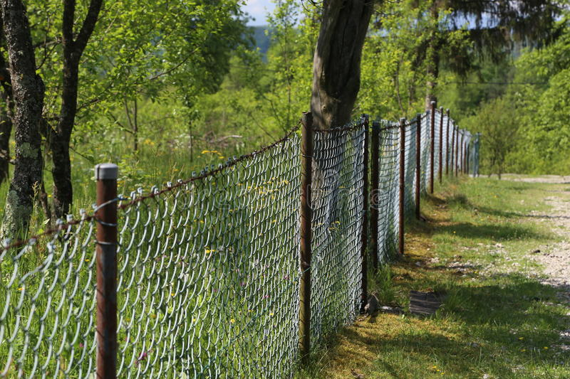 Lath fence. / Barbed wire fence on a green background royalty free stock image