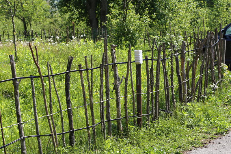 Lath fence. / Barbed wire fence on a green background royalty free stock photo