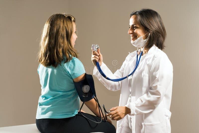 Latido del corazón de la muchacha del doctor verificaciones. Horizontal imagen de archivo libre de regalías
