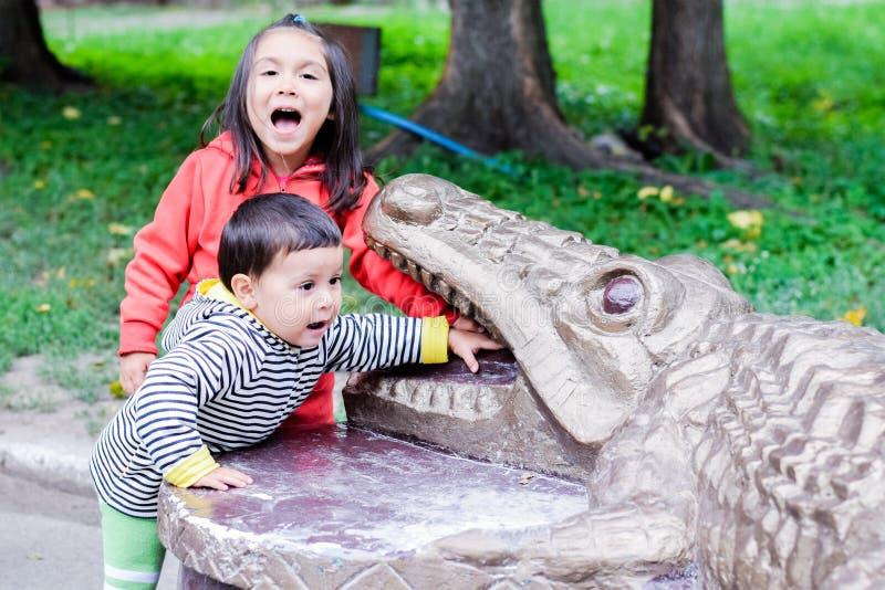 Latijn weinig sibling die en wat betreft de tanden van het monument van een krokodil gillen stock afbeelding