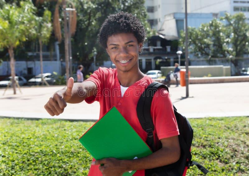 Latijns-Amerikaanse student met tandsteunen die duim tonen royalty-vrije stock foto's