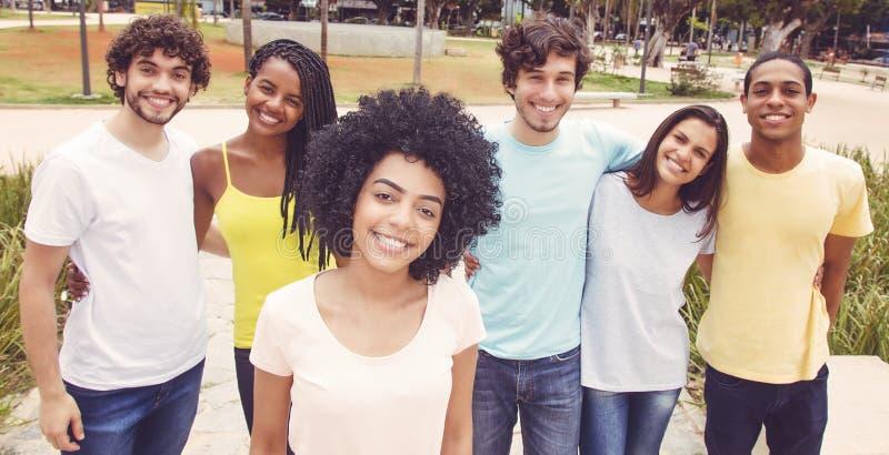 Latijns-Amerikaanse vrouw met groep vrienden in retro blik stock foto's