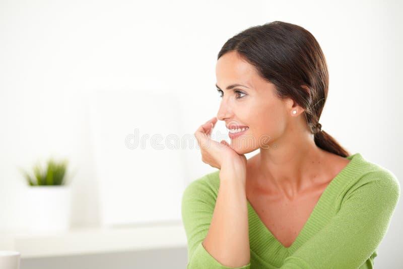 Latijns volwassen meisje die terwijl tevreden het kijken glimlachen stock afbeelding