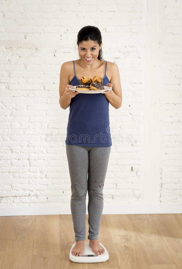Latijns vrouw of tienermeisje die gewicht controleren bij de muffin en de chocoladedoughnut van de schaalholding het glimlachen stock foto's