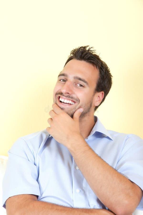 Latijnse mens die in zijn woonkamer bij camera glimlacht stock afbeeldingen