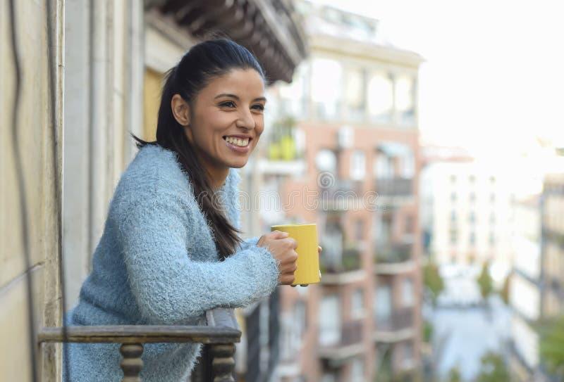 Latijnse vrouw het drinken kop van koffie of thee glimlachen gelukkig bij het balkon van het flatvenster royalty-vrije stock afbeelding