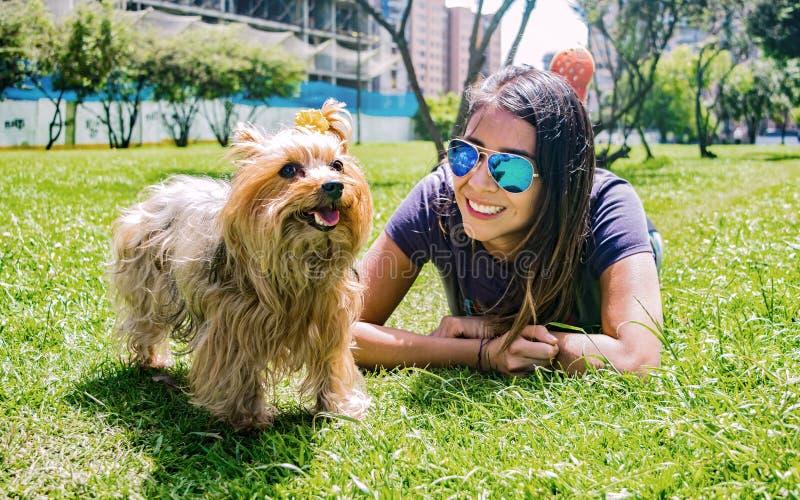 Latijnse vrouw met haar gelovige hondsvriend Yorkshire Terrier stock afbeelding