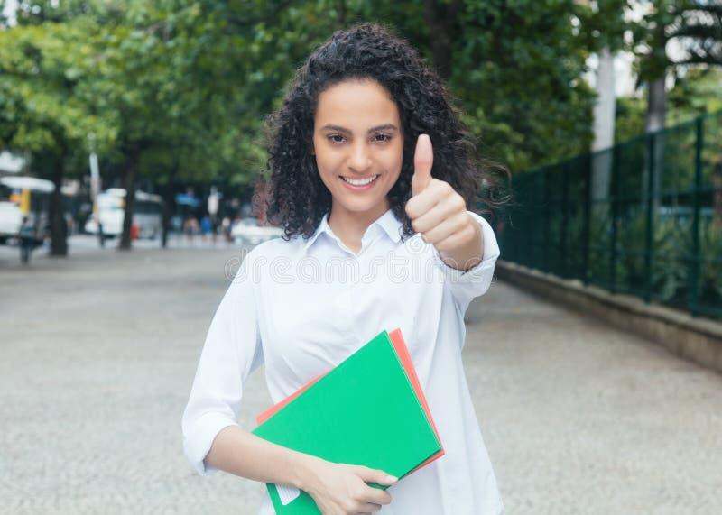 Latijnse vrouwelijke student met krullend haar en wit overhemd die thu tonen stock fotografie