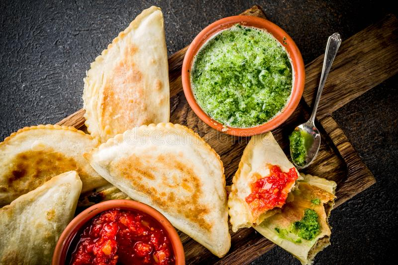 Latin American food, empanadas. Latin American, mexican, chilean food. Traditional baked pastry empanadas with beef meat, two spicy sauces, dark rusty background stock image