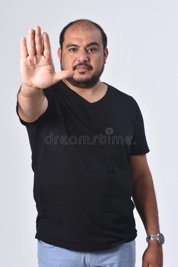 Latin american Man with stop sign white background royalty free stock image