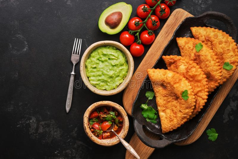 Latin American, Mexican, Chilean food. Traditional fried empanadas served with tomato and avocado sauce on a dark background. Top royalty free stock photography