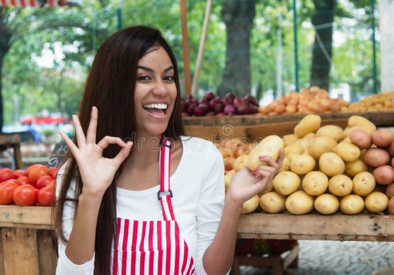 Latin - amerikansk försäljare på bondemarknaden framlägga den potatisen royaltyfria foton