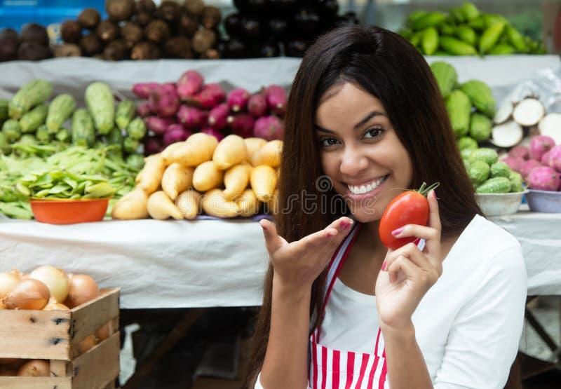 Latin - amerikansk försäljare på bondemarknaden med tomaten och vege royaltyfri foto