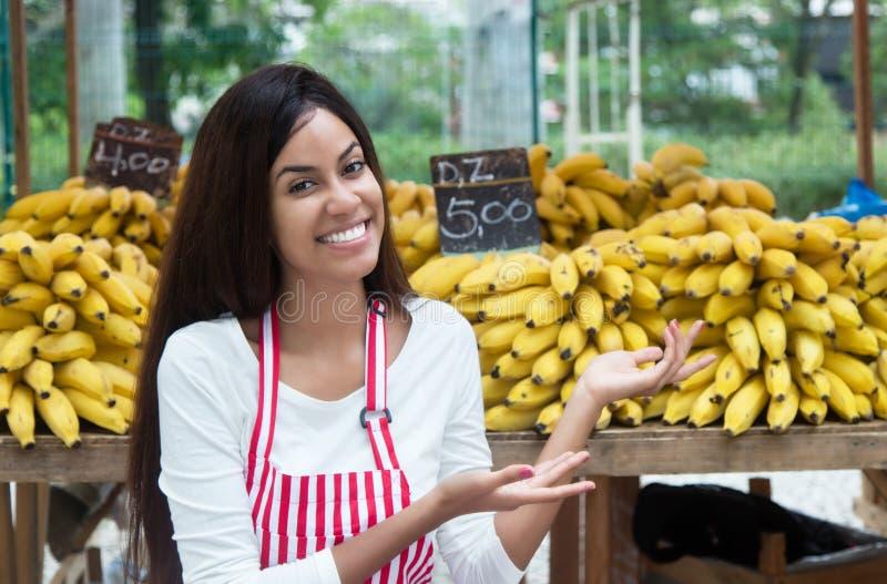 Latin - amerikansk försäljare på bondemarknaden som framlägger bananer arkivfoton