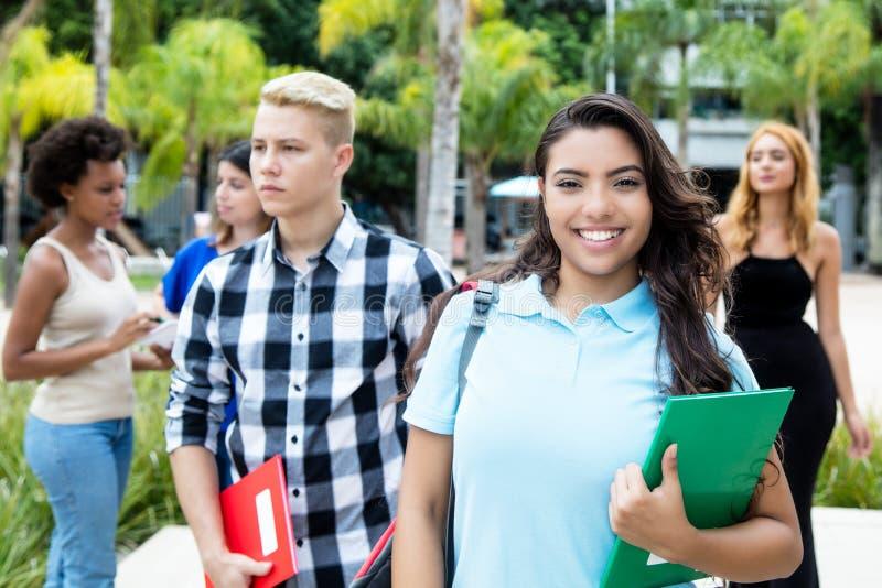 Latin - amerikansk kvinnlig student med den tonårs- caucasian och afrikanen arkivbild